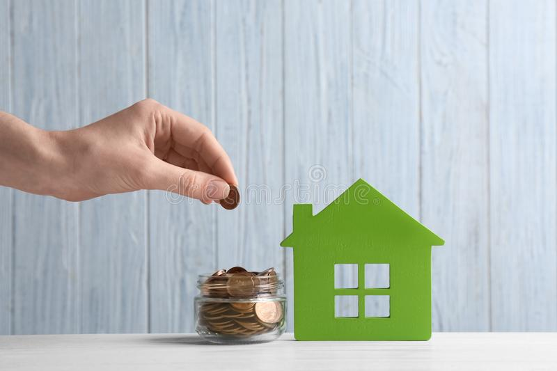 Woman putting coin into jar near house model on table against wooden background. Space for text stock photo