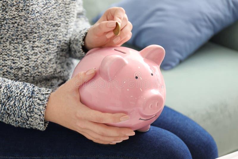 Woman putting coin into piggy bank indoors, closeup. Money savings concept stock image