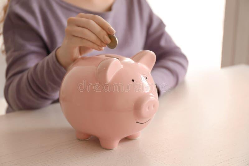 Woman putting coin into piggy bank indoors. Money savings concept stock photos