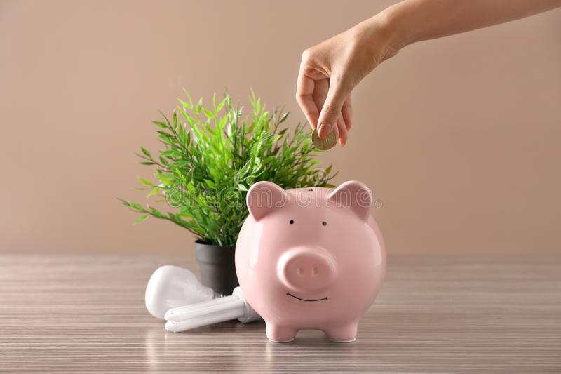 Woman putting coin into piggy bank near light bulbs on table. Electricity saving concept stock image