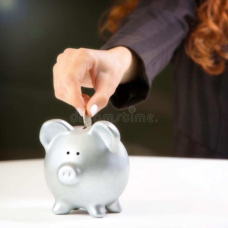 Woman putting coin in piggy bank stock image