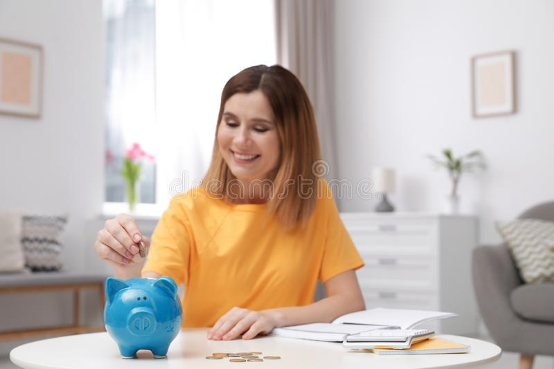Woman putting coin into piggy bank at table. Saving money royalty free stock photo
