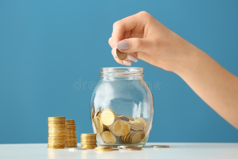 Woman putting coins into glass jar on table. Savings concept stock images
