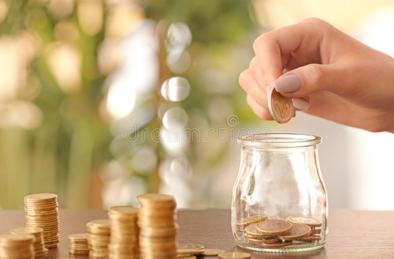Woman putting coins into glass jar on table. Savings concept royalty free stock image