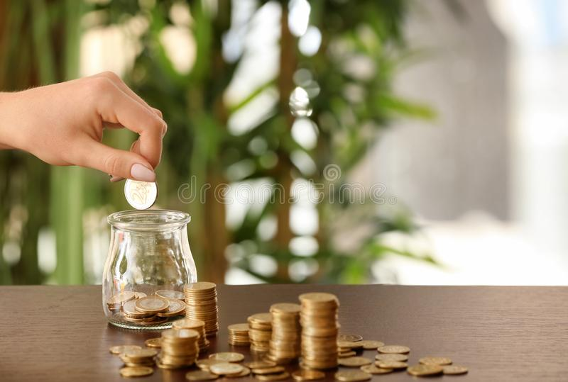 Woman putting coins into glass jar on table. Savings concept royalty free stock photo