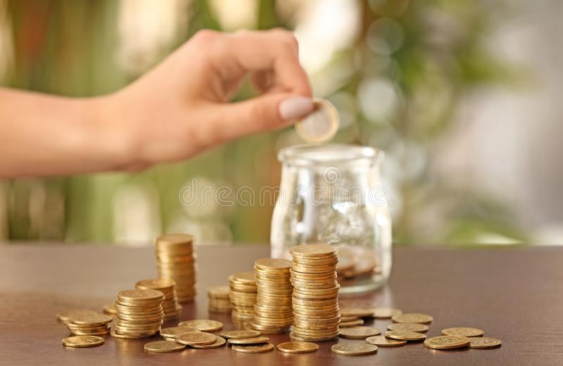 Woman putting coins into glass jar on table. Savings concept royalty free stock photography