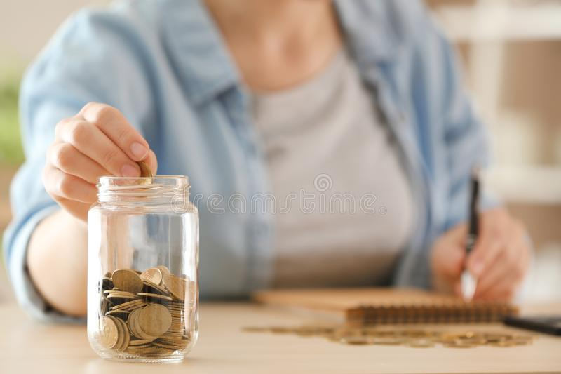 Woman putting coins into glass jar on table. Savings concept royalty free stock images