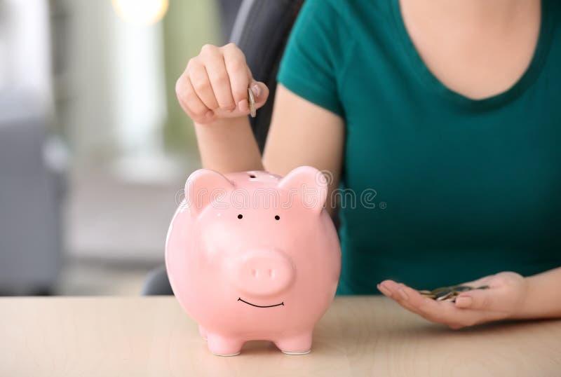 Woman putting coins into piggy bank indoors, closeup. Money savings concept stock photos