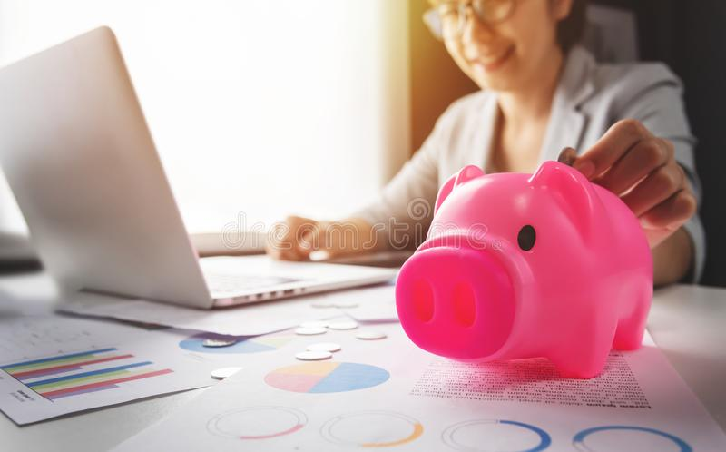 Woman putting coins into Pink Piggy Bank stock photo