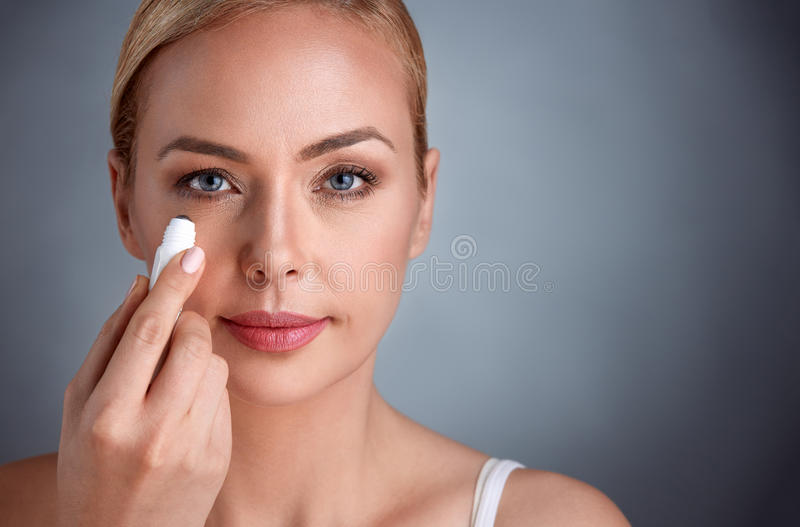 Woman putting concealer under her eyes stock photos