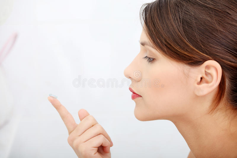Woman putting a contact lens. Beautiful young caucasian woman putting a contact lens at bathroom royalty free stock images