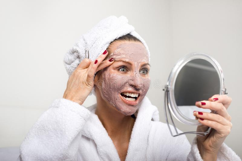 Woman putting cosmetic mask on her face royalty free stock photo