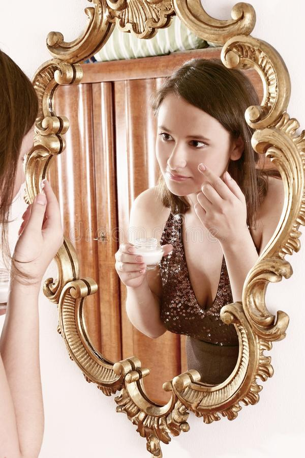 Woman putting cream in front of a mirror royalty free stock photos