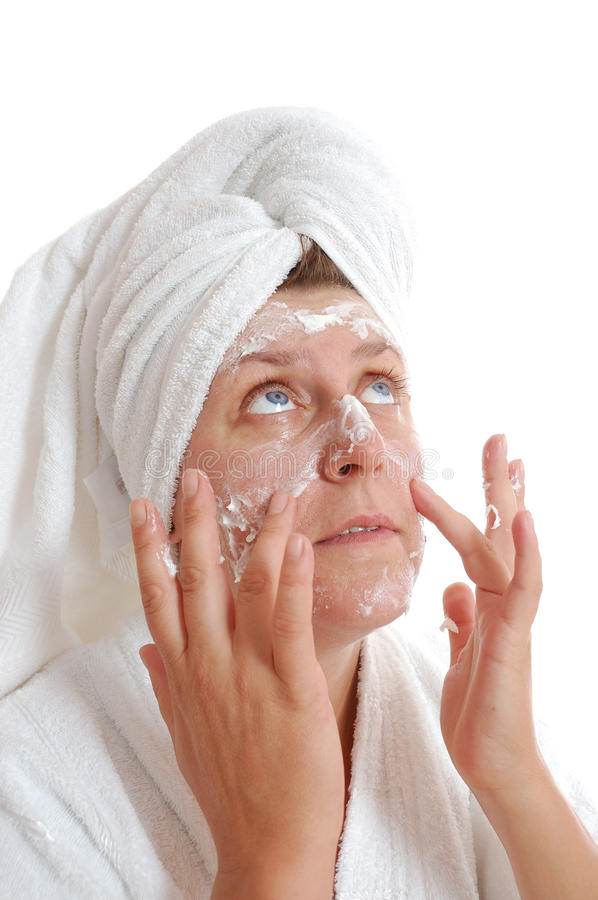 Woman Putting Cream On Her Face Stock Images