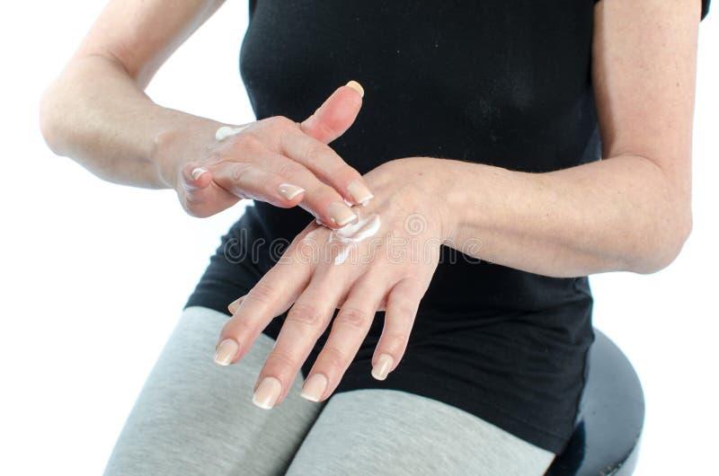 Woman putting cream on her hand stock photo