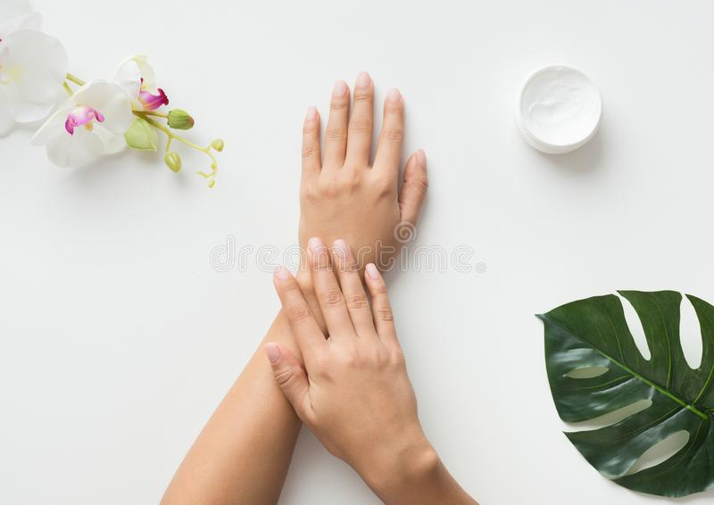 Woman putting cream on her hands on white background stock photos