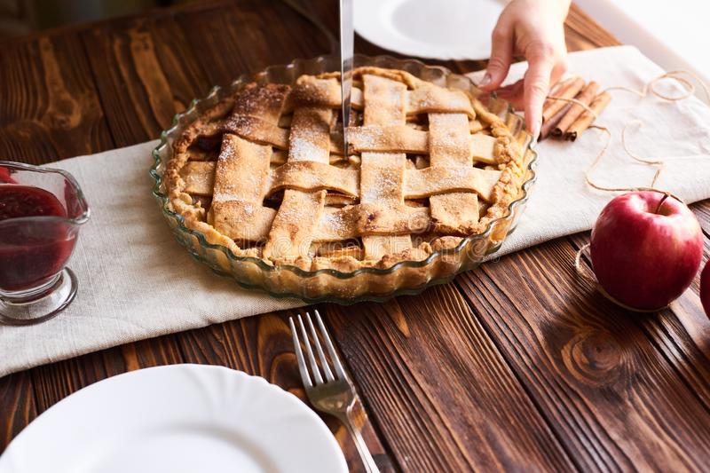 Woman putting delicious american pie on table. Close-up woman`s hands cutting a homemade apple pie. White plates on the table royalty free stock images