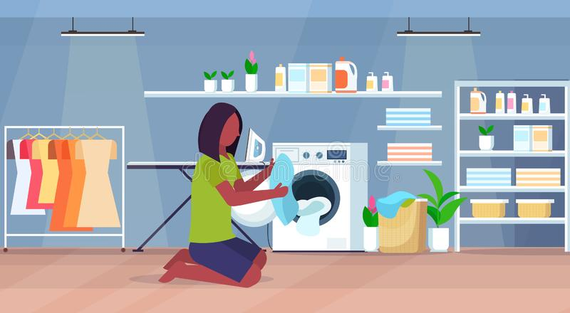 Woman putting dirty clothes into washing machine african american housewife doing housework modern laundry room interior. Cartoon character full length flat royalty free illustration