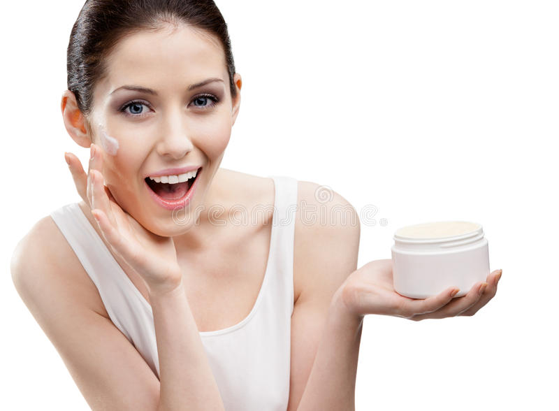 Woman putting on emollient cream from container on face stock image