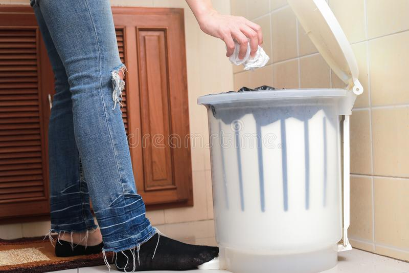 Woman putting empty plastic bag in recycling bin in the kitchen. stock image