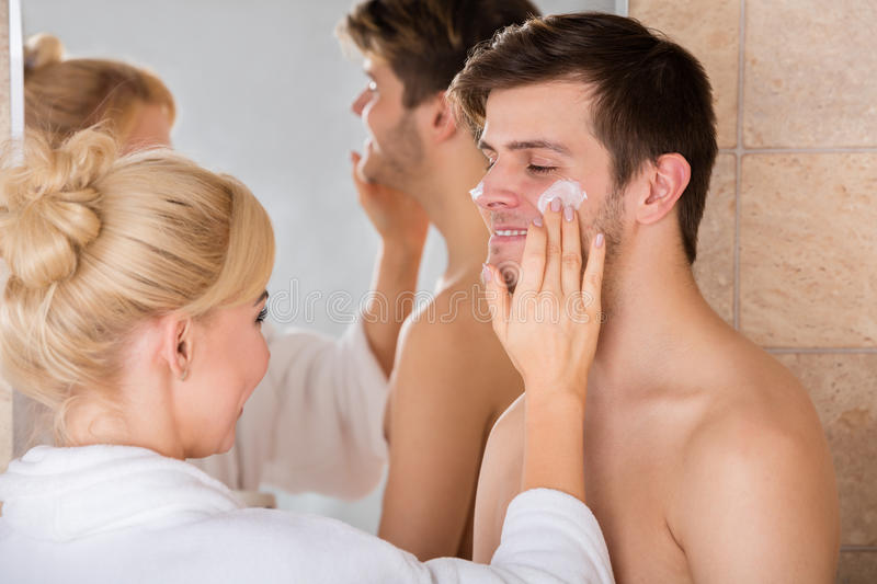 Woman Putting Face Cream On Man Nose In Bathroom royalty free stock photo