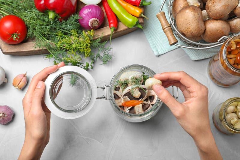 Woman putting garlic into glass jar at grey table. Pickling mushrooms royalty free stock images