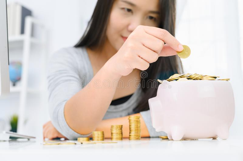 Woman putting golden coin in pink piggy bank. saving money, budget, investment, finance concept royalty free stock photo