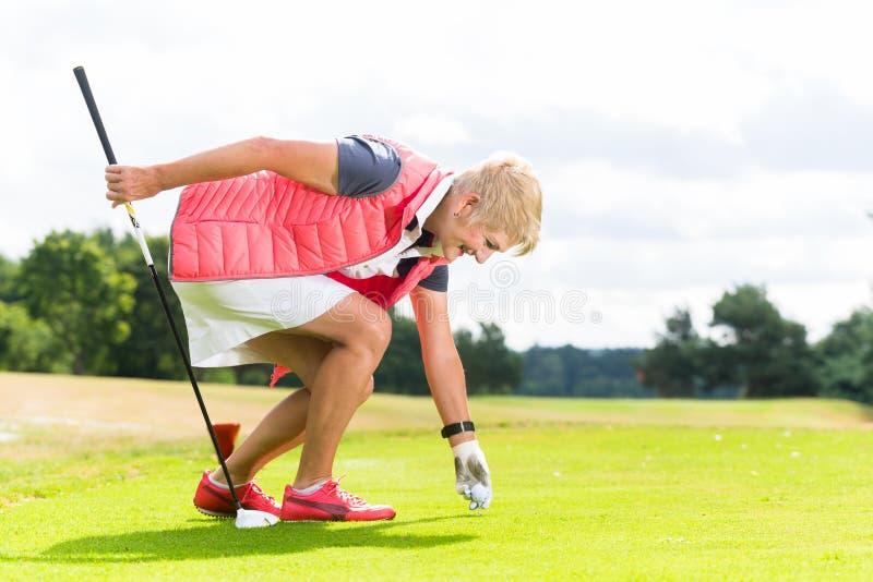 Woman putting golf ball on tee, close shot stock image
