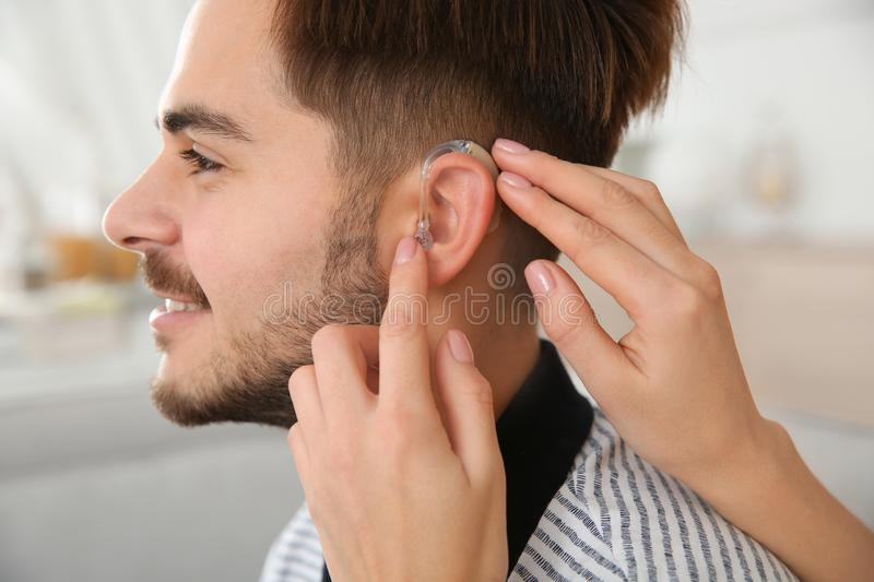 Woman putting hearing aid in man`s ear indoors. Closeup stock photos