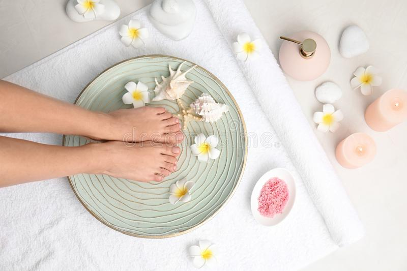 Woman putting her feet into plate with water, flowers and seashells on white towel, top view. royalty free stock photos