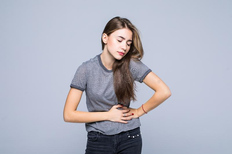 Young Woman putting her hands for belly or stomach ache on grey background. Woman putting her hands for belly or stomach ache on grey background royalty free stock image