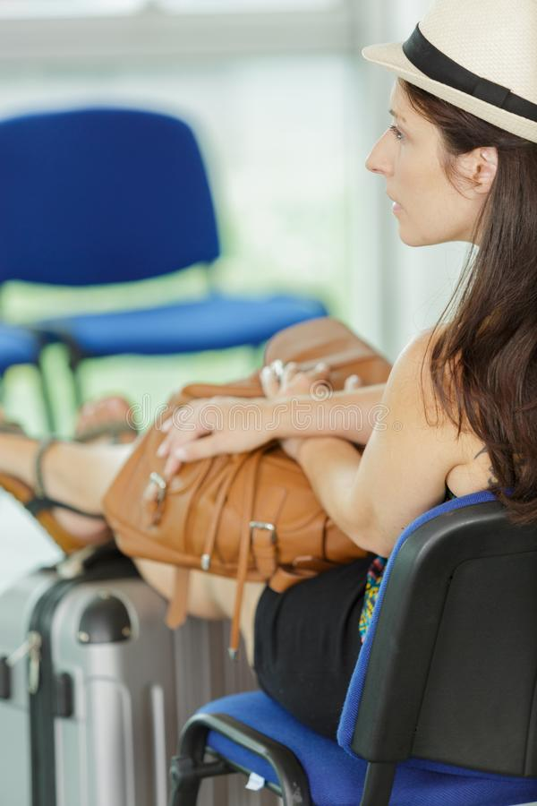 Woman putting legs up on suitcase waiting stock photo