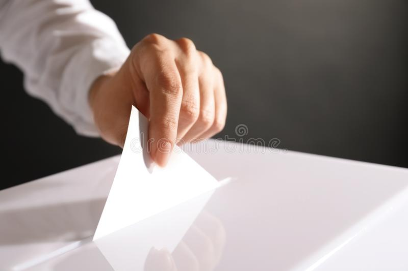 Woman putting her vote into ballot box. On black background, closeup royalty free stock photo