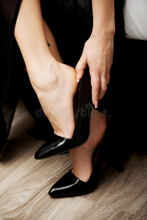 Woman putting on high heels. royalty free stock photos