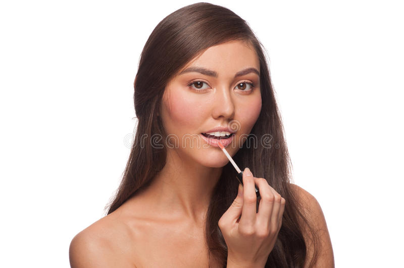 Download Woman putting on lip gloss stock photo. Image of cosmetic - 27197204