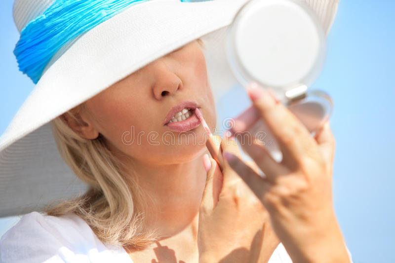 Woman Putting Lipstick Stock Image