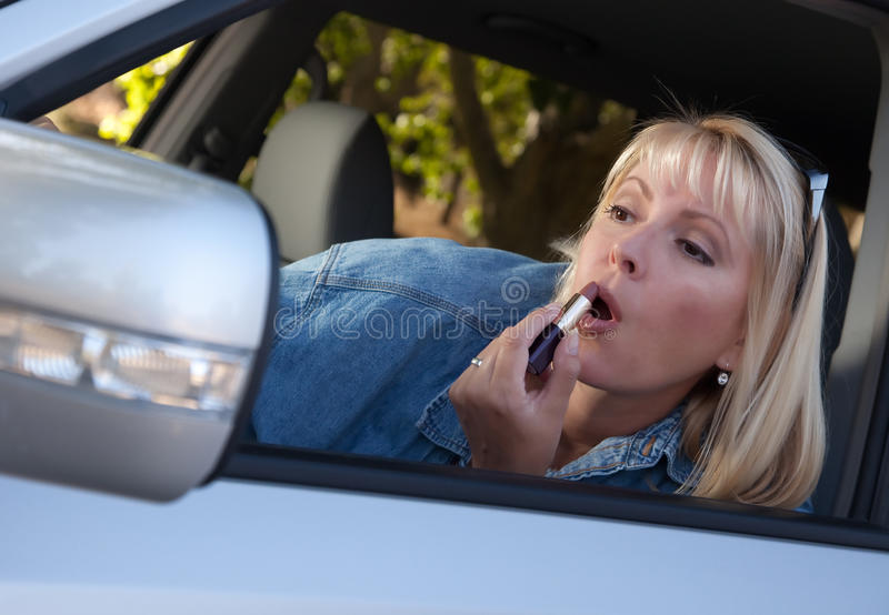 Download Woman Putting On Lipstick While Driving Stock Photo - Image: 11067596