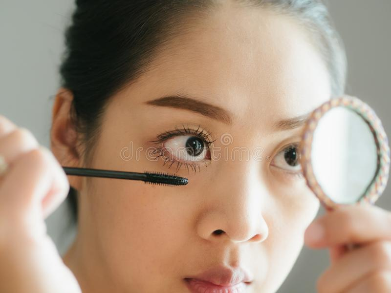 Woman is putting make up mascara on her eyelashes. Asian woman is putting make up mascara on her eyelashes royalty free stock images