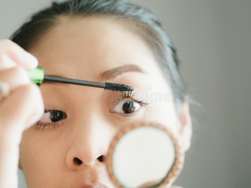 Woman is putting make up mascara on her eyelashes. Asian woman is putting make up mascara on her eyelashes royalty free stock photo