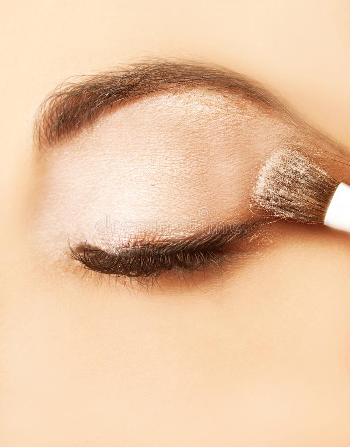 A woman putting on makeup on her eyelid stock images