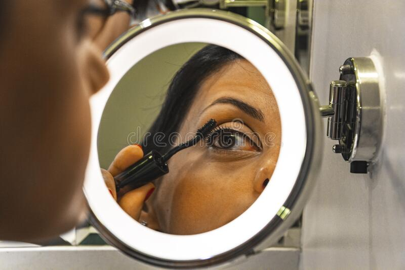 Woman putting makeup on at home royalty free stock image