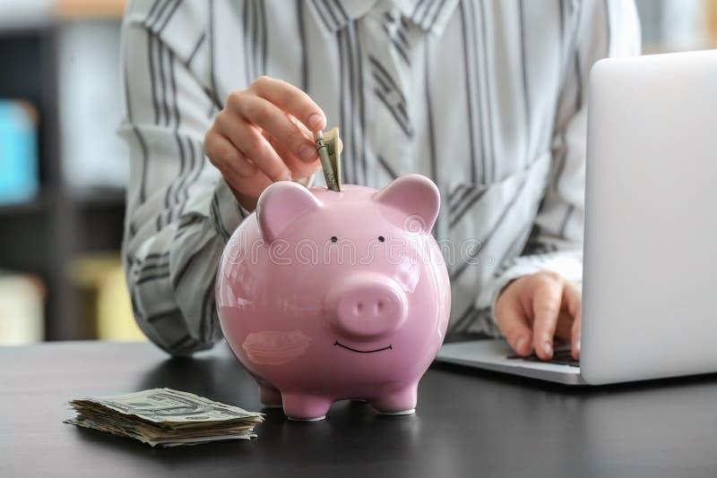 Woman putting money into piggy bank. Savings concept stock photos