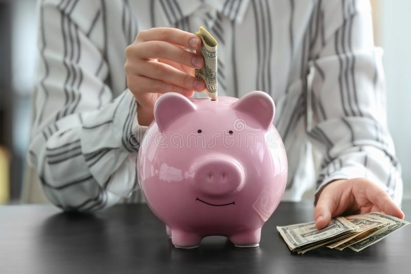 Woman putting money into piggy bank. Savings concept royalty free stock photo