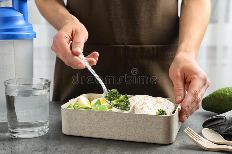 Woman putting natural protein food into container on table, closeup royalty free stock photos
