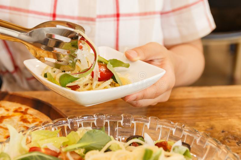 Woman putting noodles into the dish. On her hand royalty free stock images