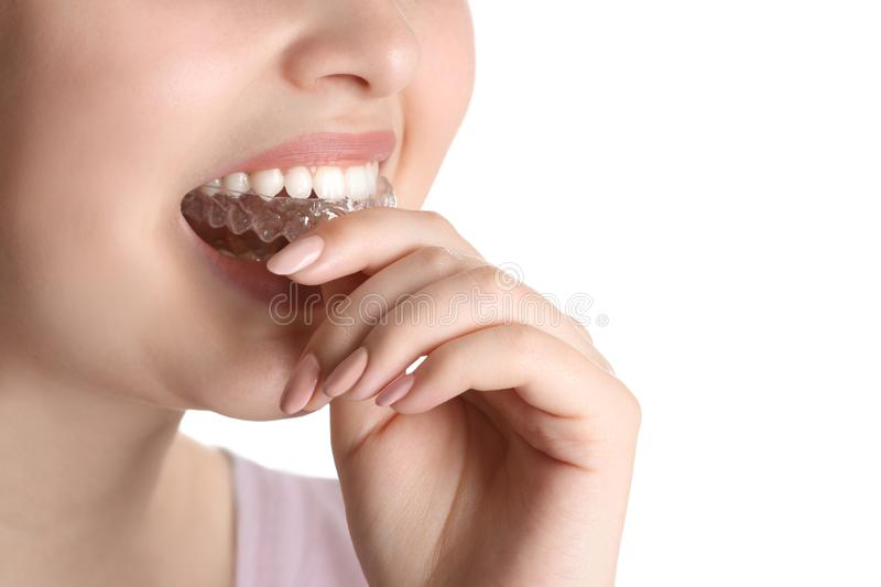 Woman putting occlusal splint in mouth on white background, closeup royalty free stock photography