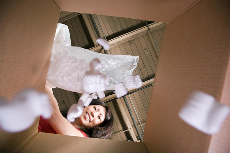 Woman putting packing peanuts in box royalty free stock photography