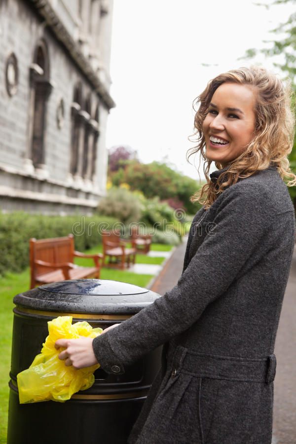 Woman putting plastic waste in garbage bin royalty free stock photos
