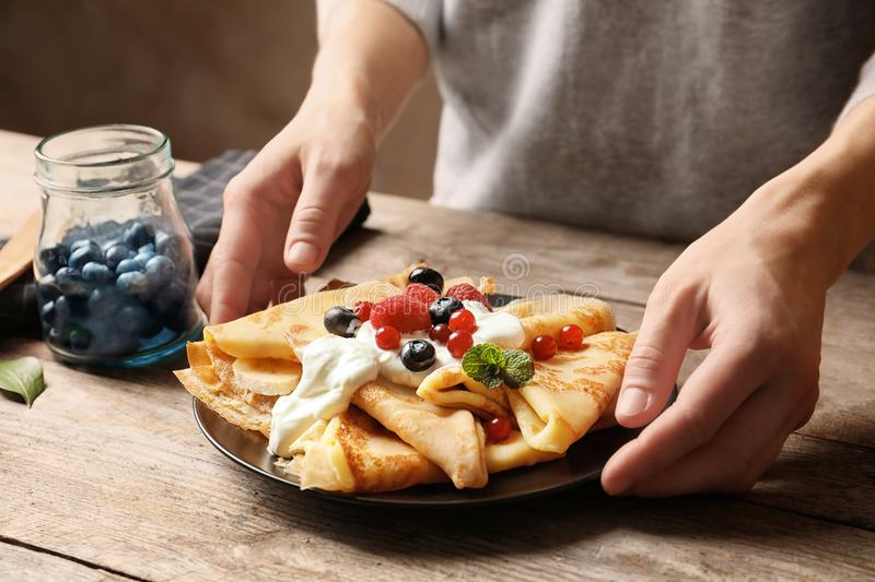 Woman putting plate with thin pancakes, berries royalty free stock image