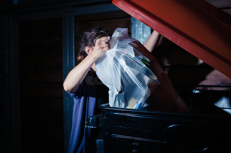 Woman putting rubbish in bin. A young woman is putting a bag of rubbish in a large bin at night royalty free stock photos